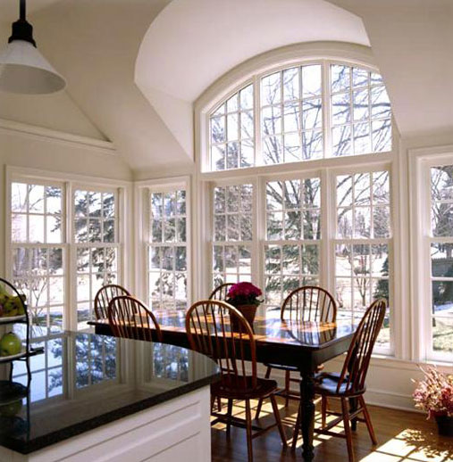 Big beautiful kitchen dining room with lots of sunlight through the glass windows