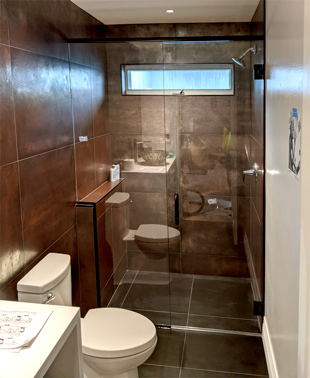 Heavy glass shower has black hardware (Waunakee)