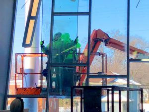 Our guys installing the glass into custom angled window framing in a commercial building