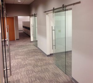 Sliding glass doors for office hang from handsome pipe above door