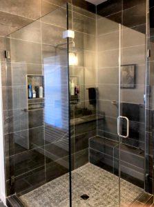 frameless clean design shower in dark tiled bathroom