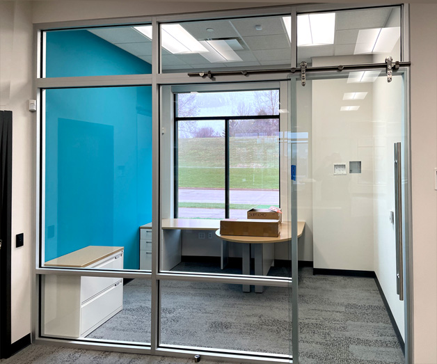 glass office wall with barn door sliding door