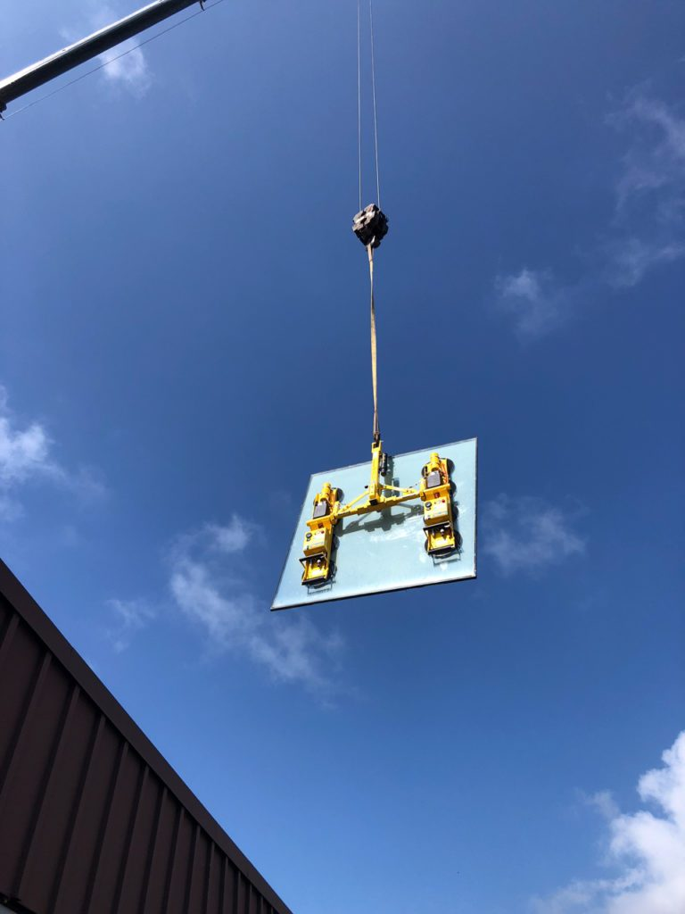 Power cup vacuum lifting system hangs from a crane to install heavy glass units.