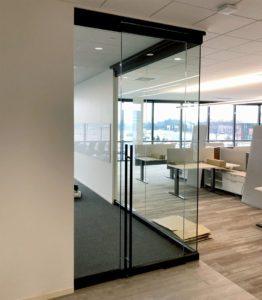 Interior glass corner office has swing door with custom ladder handle