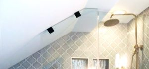 Close up of custom frameless shower door for bathroom snuggled into the sloped ceiling of the eaved roof
