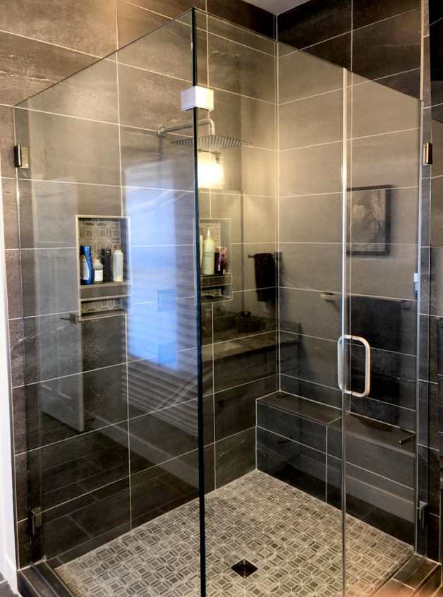 frameless clean design shower in dark tiled bathroom
