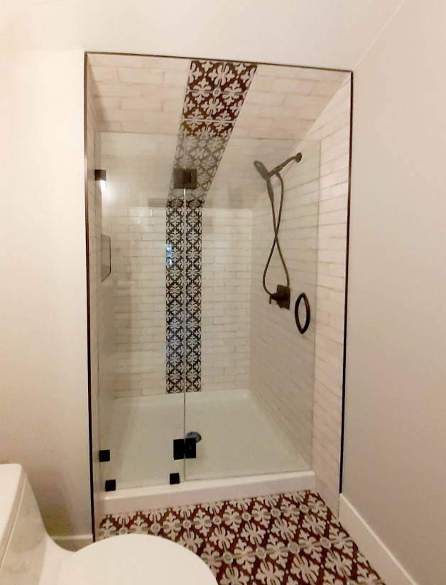 headerless shower door has black hardware